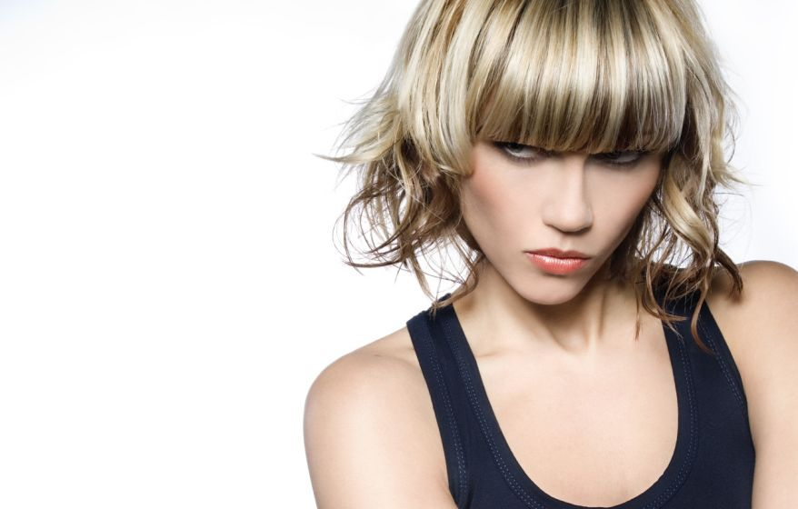 Woman with short blond hair with a mean look on her face