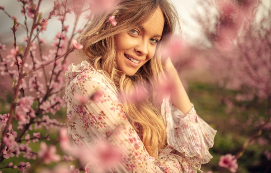 Amazing young woman posing in apricot tree orchard at spring