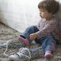 Baby trying on big shoes