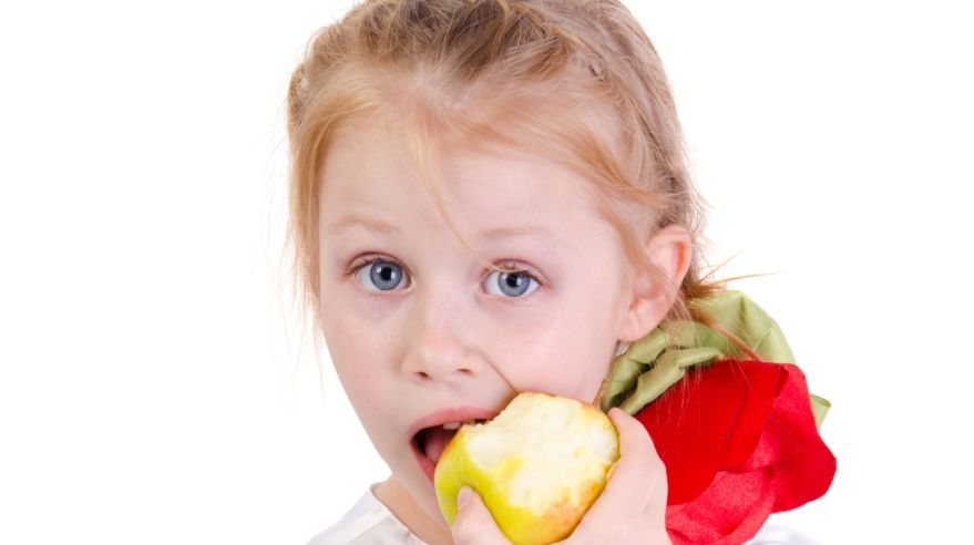 beautiful young girl eating an apple isolated on white