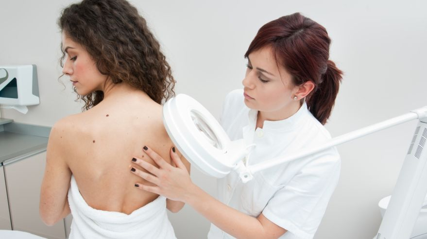 Young woman's back being examined at a dermatologists