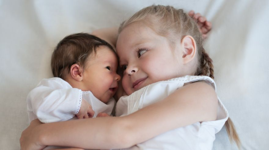 Sister hugs her younger brother