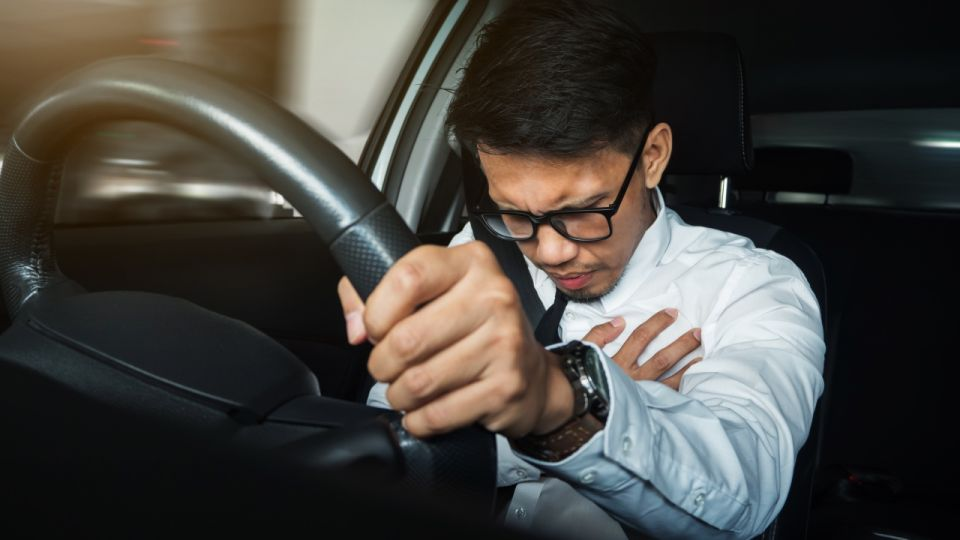 Asian businessman having heart attack while he driving car.