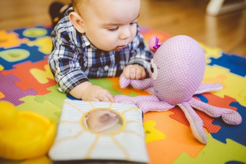 Baby Boy Flooring Surrounded By Lots Of Toys