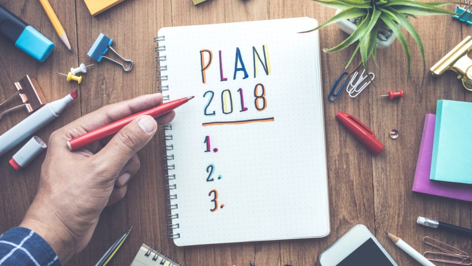 PLAN 2018 message with male hand writing on notepad paper