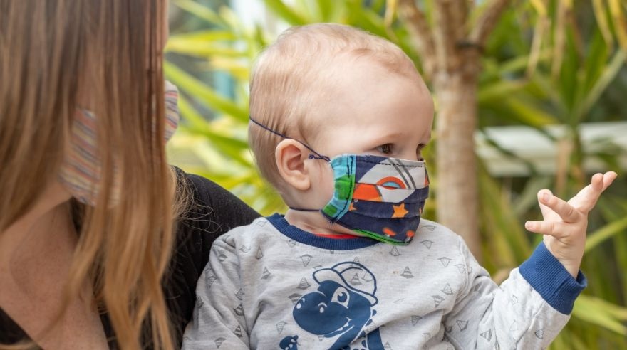 Portrait of mother and baby in homemade reusable protective face mask