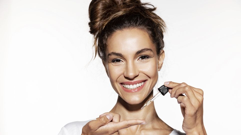 Young woman holding  face oil.