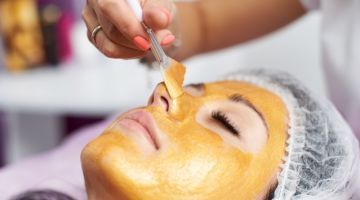 Macro photography of the hand of the beautician with the help of a special brush puts on the face of the girl a golden mask in the spa