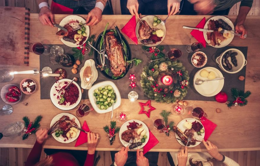 people eating traditional christmas meal at festive wooden table