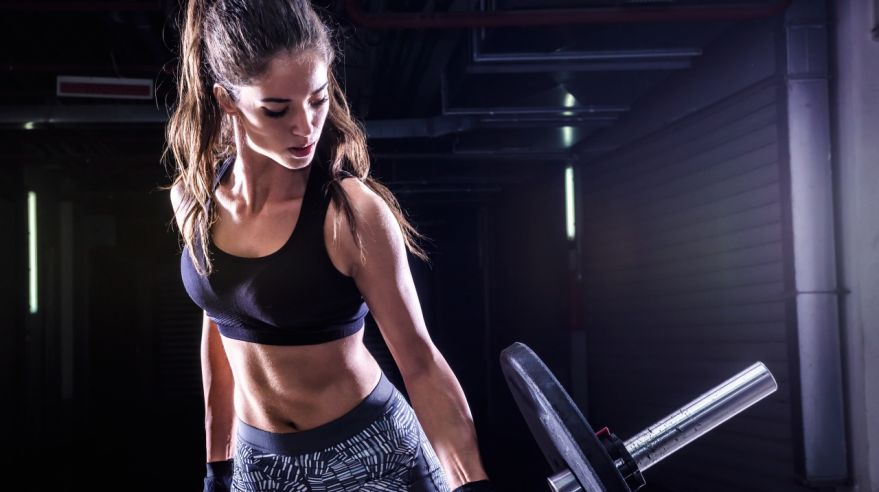 Attractive young fit sportswoman working out with weights