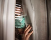 Young woman in quarantine wearing a mask and looking through the window