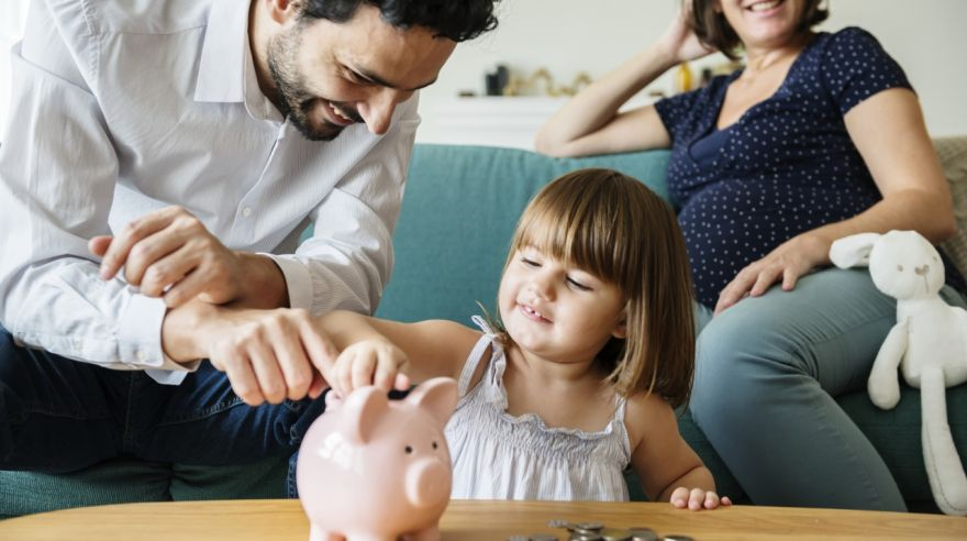 Family saving money in piggy bank