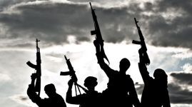 Silhouette of Muslim militants with rifles