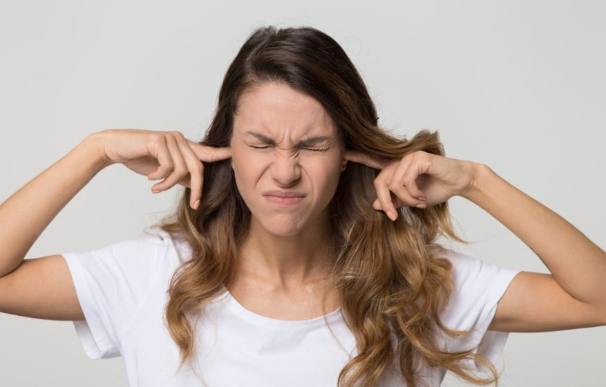 Stubborn woman sticking fingers in ears not listening to noise