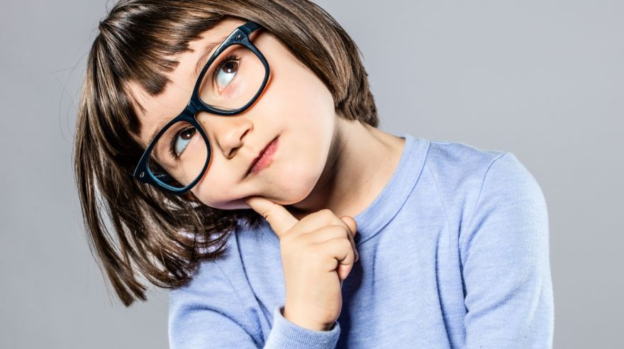 thoughtful beautiful little girl with intelligent eyeglasses to imagine