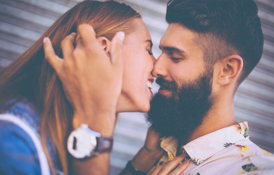 Bearded hipster guy and girl about to kiss happily
