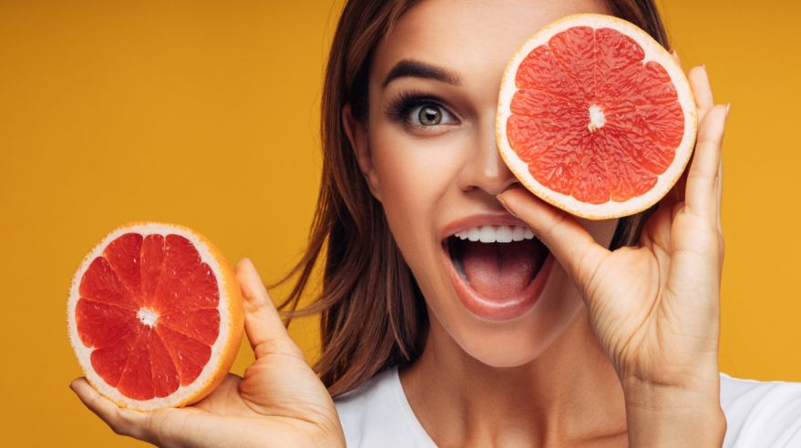 Portrait of girl holding red grapefruit