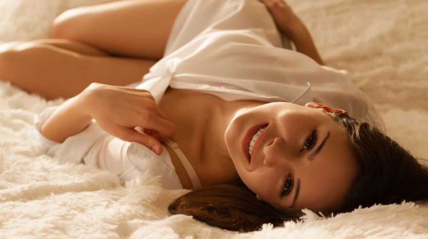 Sensual happy woman in white shirt relaxing on the bed