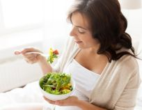happy pregnant woman eating salad at home