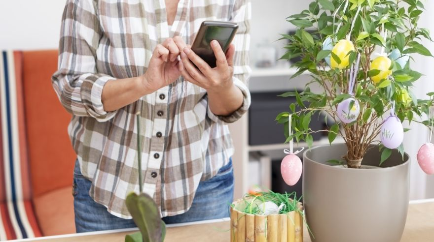 Senior woman decorating potted plant with Easter eggs