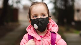 Little girl wearing pollution mask.