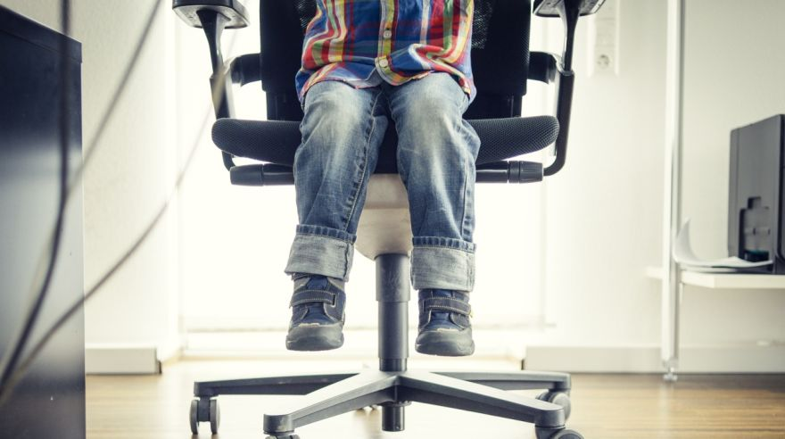 Preschooler Sitting at Grown-ups Office Desk, View of Feet