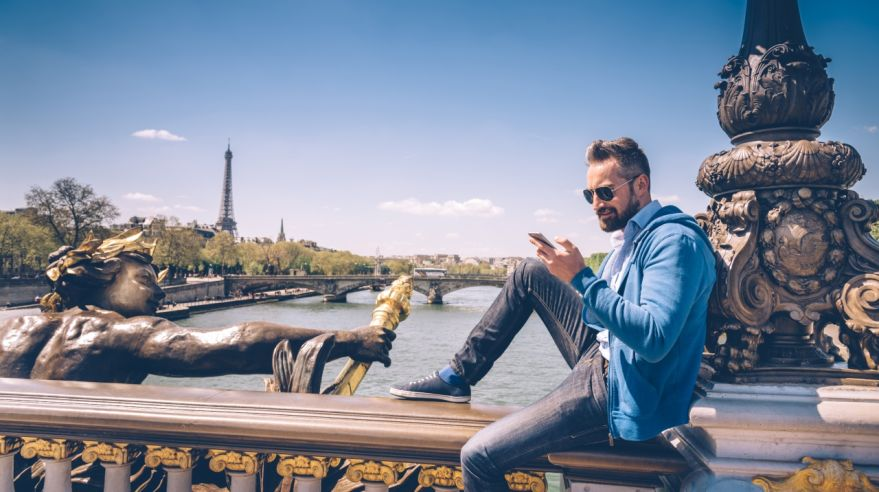 bearded man with mobile sitting on Pont Alexandre in paris