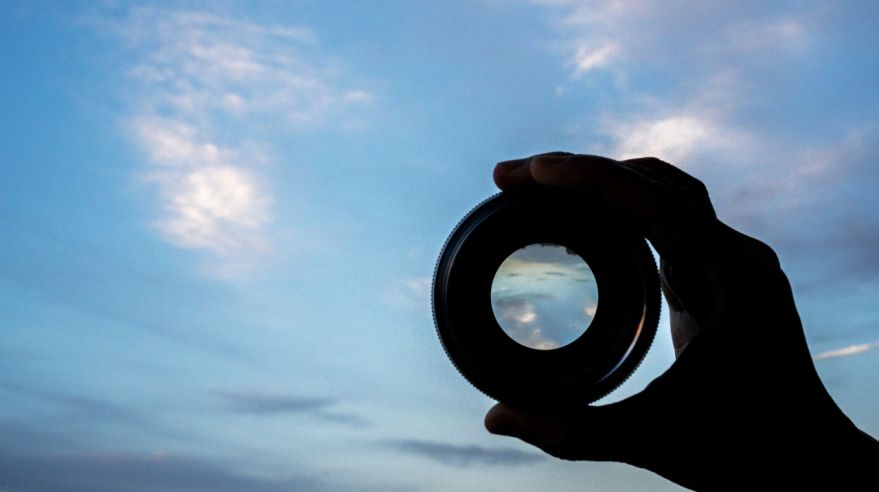 hand holding lens watching cloudscape