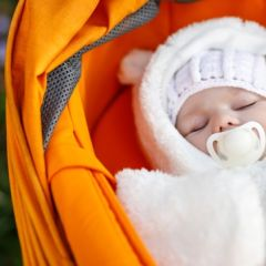 Portrait of adorable newborn baby in warm winter clothes