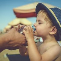 Child drinking water on the beach on summer vacations
