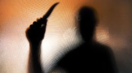 Violent threatening silhouette of man wielding a knife behind frosted glass window