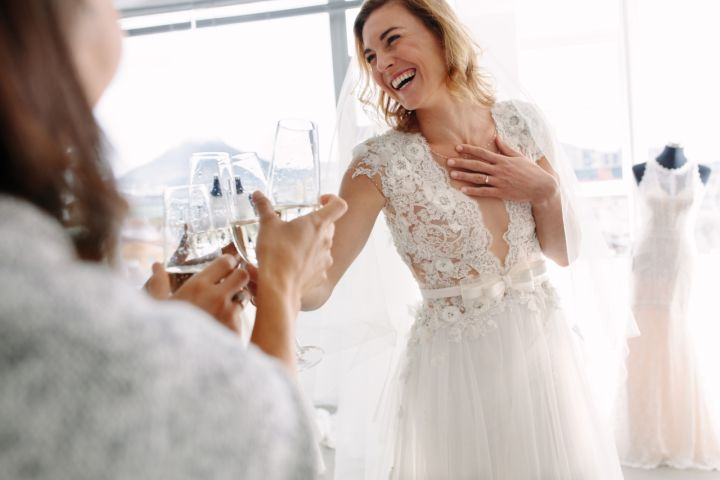 ccd912b34913 Bride toasting champagne with friends in bridal boutique
