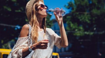 Trendy woman drinking a water from bottle, outdoors.