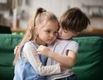 Little boy brother consoling and supporting upset girl embracing sister