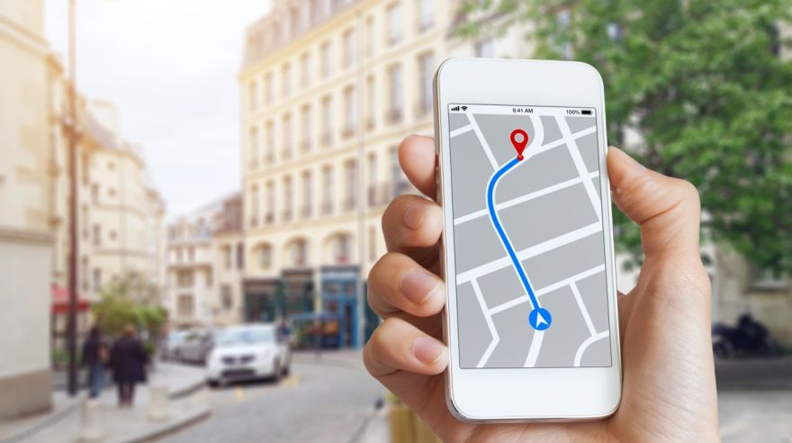 Tourist using GPS map navigation app on smartphone screen, direction