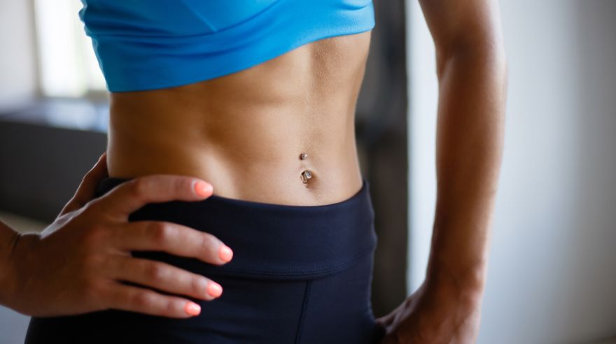 Fit woman with perfect six-pack abs close up