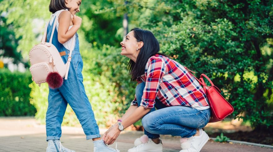 Smiling mother tying shoelaces of her daughter in the park