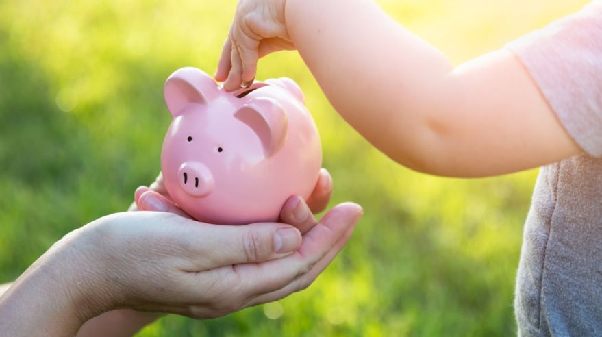 Woman Holds Piggy Bank While Baby Boy Puts Coins Inside