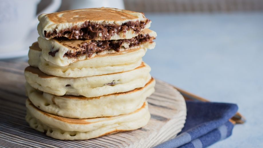 Stack of Stuffed chocolate nutella pancakes on vintage wooden board on blue table background with cup of tea. American Breakfast Concept. Copy space
