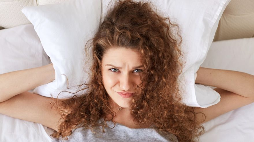 Depressed frustrated female covers ears with pillow while lies in bed, can`t stand someone`s snoring, can`t get asleep, suffers from insomnia. Curly young woman has some problems with sleep.