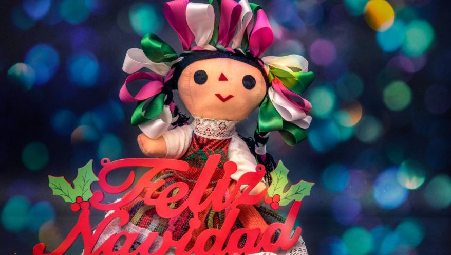 Mexican doll with colored ribbons and little girl hanging, christmas background with tree and spheres