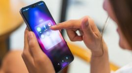 Asian woman using social media application on Huawei P20 pro smartphone, pointing at facebook app. Illustrative Editorial content.
