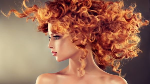 Pretty red haired girl with curly hairstyle.
