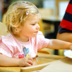 Adorable toddler girl eating healthy vegetables and unhealthy french fries potatoes. Cute happy baby child taking food from parents dish in restaurant