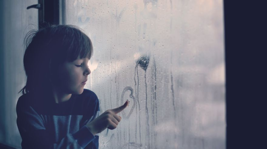 Little boy, leaving finger prints and drawing hearts on a window