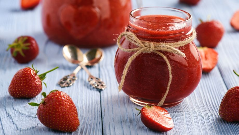 Strawberry jam in glass jar on wooden background.