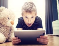 Boy and a teddy bear are watching a movie on a digital tablet