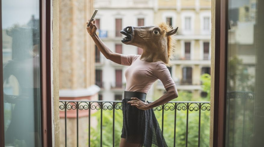 Horse mask woman selfie on a balcony