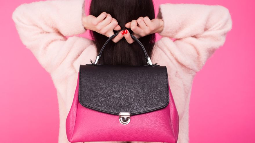 Woman in a pastel pink coat holding handbag with two hands behind the back