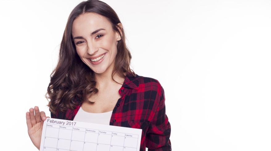 Beautiful girl smiles and holds in her hands a calendar
